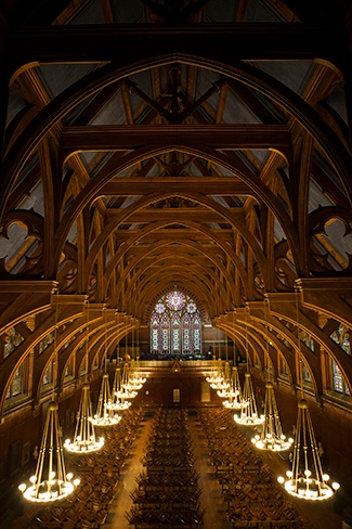 View of Annenberg Hall inside Memorial Hall at Harvard University with Chandeliers on and Stained Glass Windows